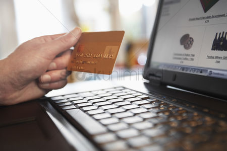 Shopping : Man holding credit card in front of laptop close up