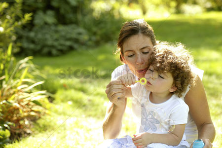Park Outdoor : Mother and daughter playing with soap bubbles