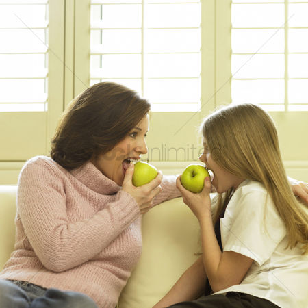 Girl : Mother and daughter sitting on the couch eating green apples