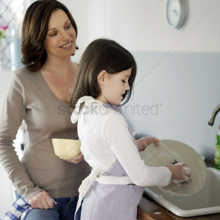 Girl : Mother and daughter washing the dishes together