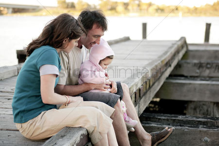 Cute : Parents and daughter sitting at the pier