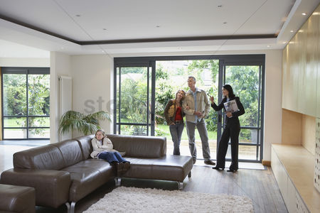 Interior : Parents with bored daughter  7-9  and estate agent observing new property