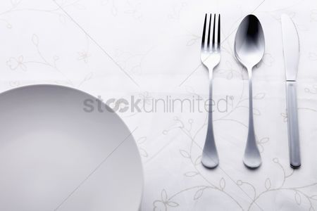 Food : Place setting of fork  spoon and table knife beside plate