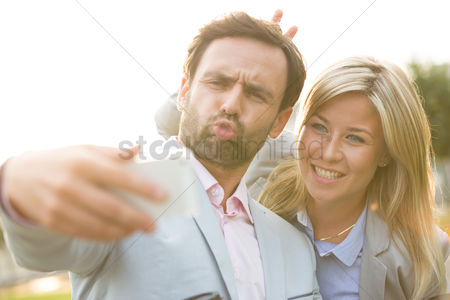 Selfie : Playful business couple taking selfie outdoors on sunny day