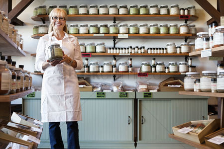 Food : Portrait of a happy senior merchant standing with spice jar in store