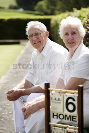 Park Outdoor : Senior couple sitting on a bench in a bowling green