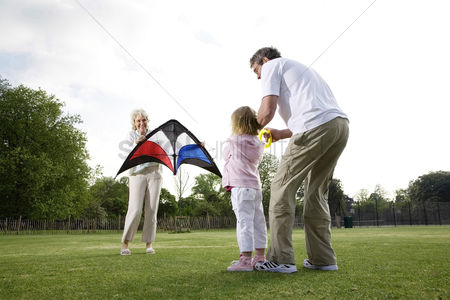 Park Outdoor : Senior man and woman playing kite with girl