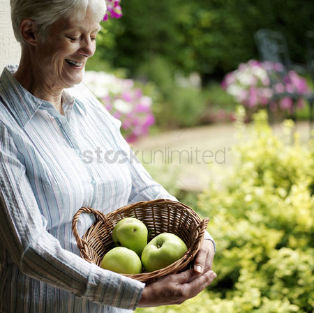Park Outdoor : Senior woman holding a basket of fruits