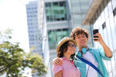 Selfie : Smiling couple taking self portrait outside office building