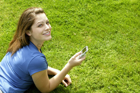 Park Outdoor : Teenage girl lying forward on the field playing with her mobile phone