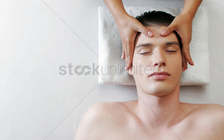 Spa : Top view of a pair of hands massaging the head of a man