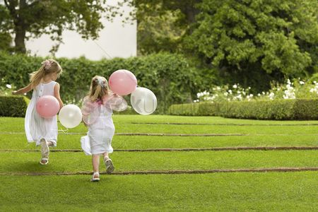 Party : Two young girls running in garden holding balloons back view