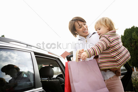 Cute : Woman carrying her daughter while holding shopping bags