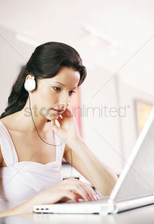 Music : Woman listening to music on the headphones while using laptop