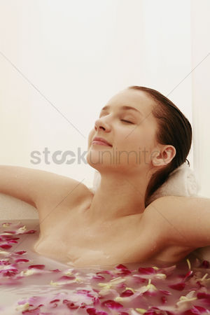 Spa : Woman relaxing in bathtub with flower petals