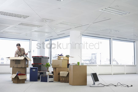 Interior : Woman with cardboard boxes in empty office space