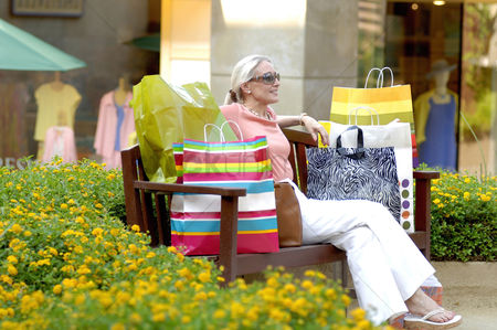 Shopping : Woman with paper bags sitting on the bench