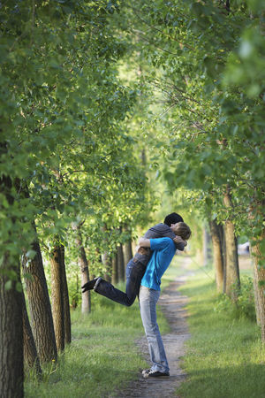 Romantic : Young couple hugging on tree lined path