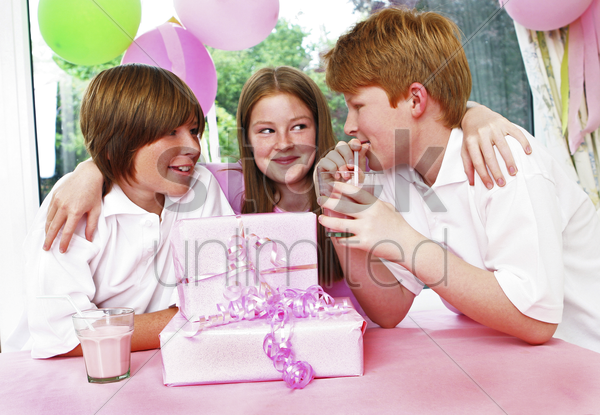 a girl hugging her two brothers stock photo