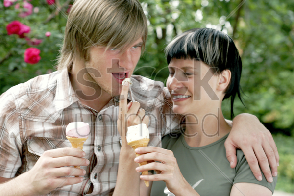 a man licking ice-cream from his girlfriend's finger stock photo