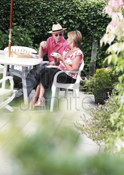 a married couple chatting and drinking in the backyard stock photo