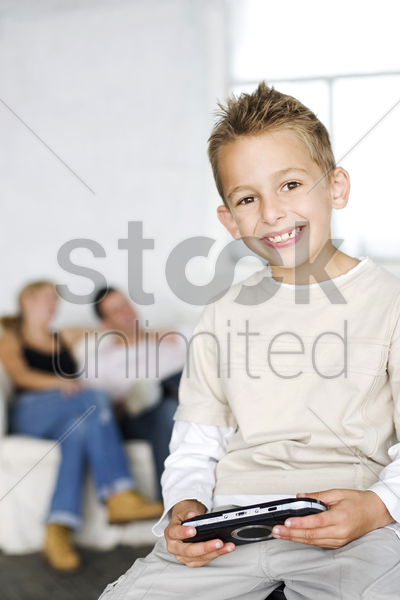 boy playing with portable video game, his parents in the background stock photo