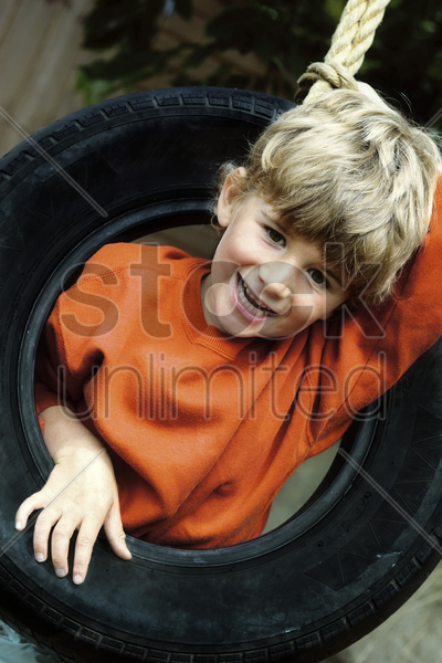 boy pushing his head out through a tyre hole stock photo