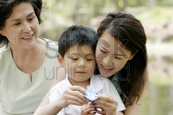 boy watching his mother making origami stock photo