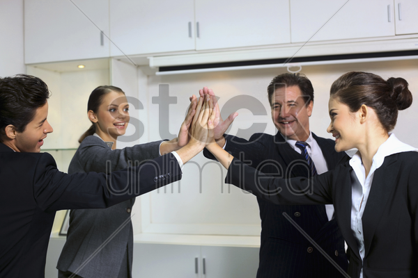 business people giving high-five at board room stock photo