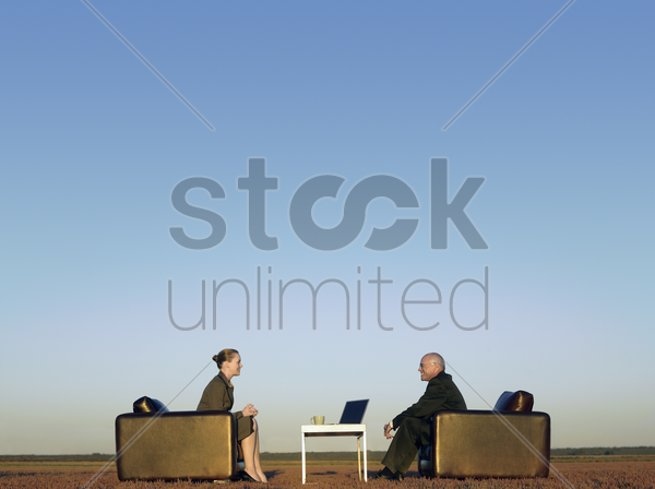 business people sitting in chairs on open plain stock photo