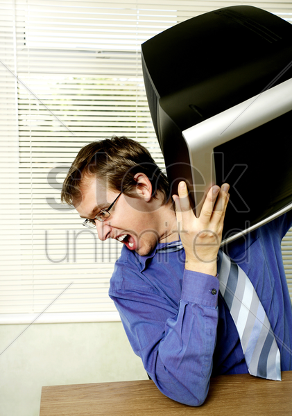 businessman about to throw his computer monitor stock photo