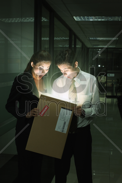 businessman and businesswoman looking into box with light emerging stock photo