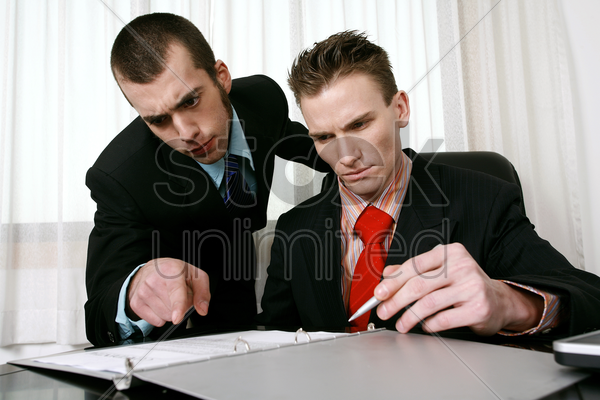 businessman and his assistant reading through a contract stock photo