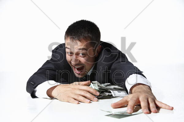 businessman gathering all the money on floor stock photo