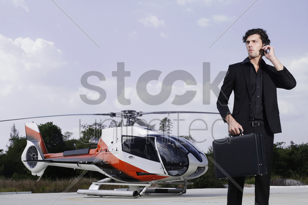businessman talking on the phone with helicopter in the background stock photo