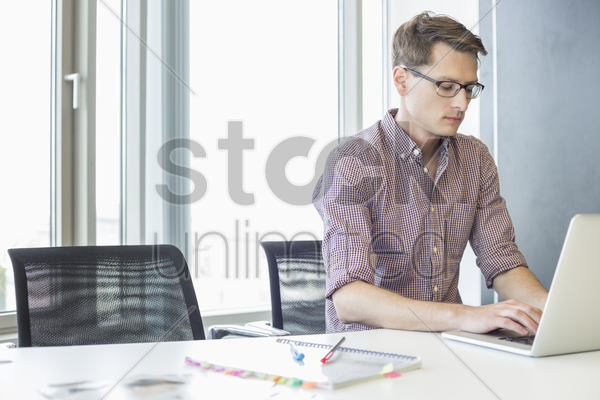 businessman using laptop at desk in creative office stock photo