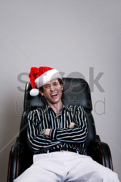 businessman with christmas hat sitting on the chair laughing stock photo