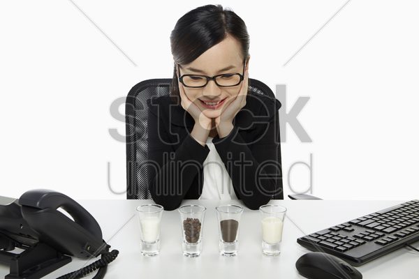 businesswoman looking at an assortment of shot glasses stock photo