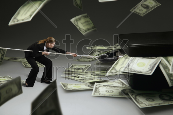 businesswoman pulling a giant briefcase with cash inside stock photo