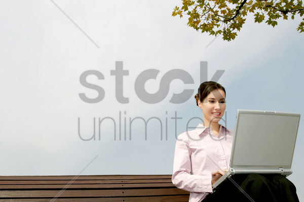 businesswoman sitting on the bench using laptop stock photo