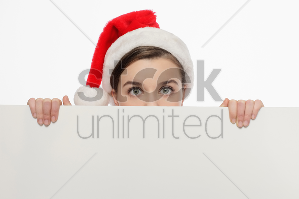 businesswoman with santa hat peeking from behind a white board stock photo