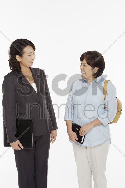 businesswomen smiling at each other stock photo