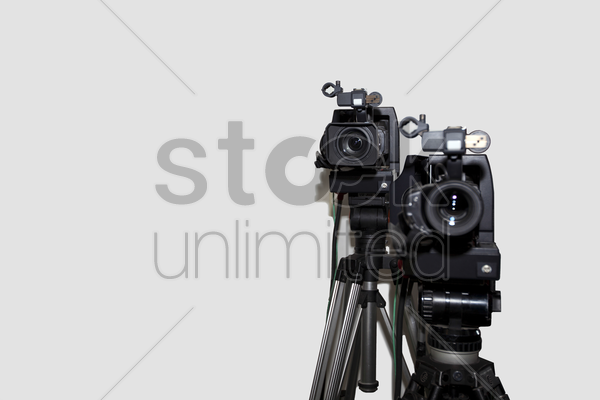 camera and tripod against white background stock photo