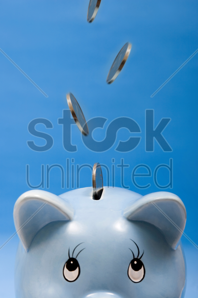 coins dropping into a piggy bank slot stock photo