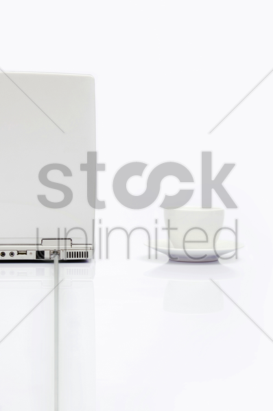 computer laptop with cup and saucer stock photo