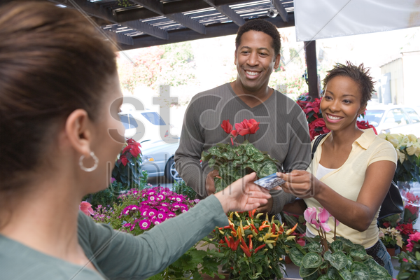 couple purchasing plants in shop stock photo