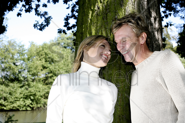 couple smiling while looking at each other stock photo