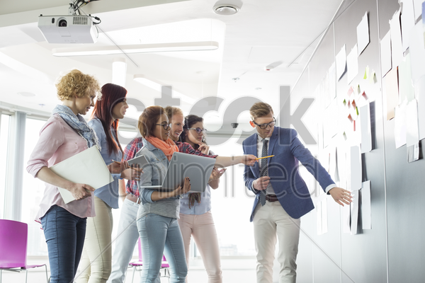 creative businesspeople discussing over documents on wall in office stock photo