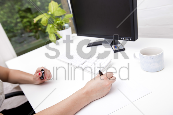 cropped image of businesswoman noting on paper at computer desk stock photo