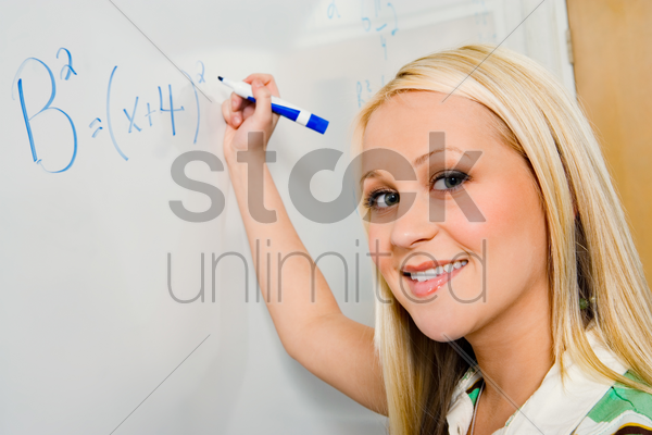 female student writing equation on whiteboard (portrait) stock photo